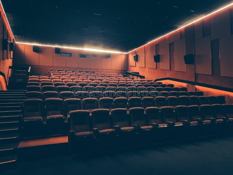 Filmbiograf med många röda platser eller stolar i mörk tom salong fotografering för bildbyråer