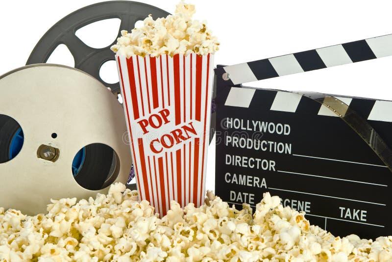 FilmClapperbräde i popcorn med filmrullen arkivbild