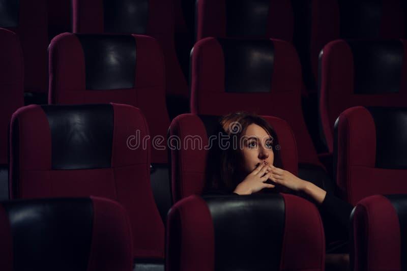 Filme de observação da menina assustado nova no teatro do cinema fotos de stock royalty free