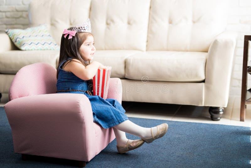 Filme de observação da princesa pequena em casa fotografia de stock royalty free