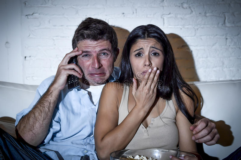 Filme de observação da televisão do abraço do sofá do sofá dos pares em casa que olha junto o grito triste comprimido fotografia de stock