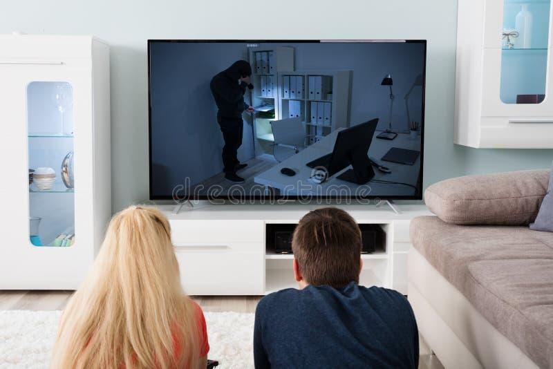 Filme de observação do suspense dos pares na televisão imagens de stock royalty free