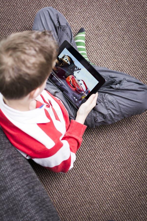 Filme de observação dos carros do menino no PC da tabuleta imagens de stock
