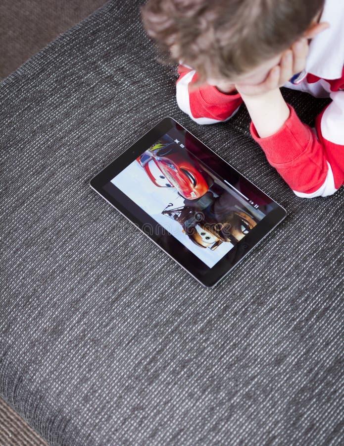 Filme de observação dos carros do menino no PC da tabuleta fotos de stock royalty free