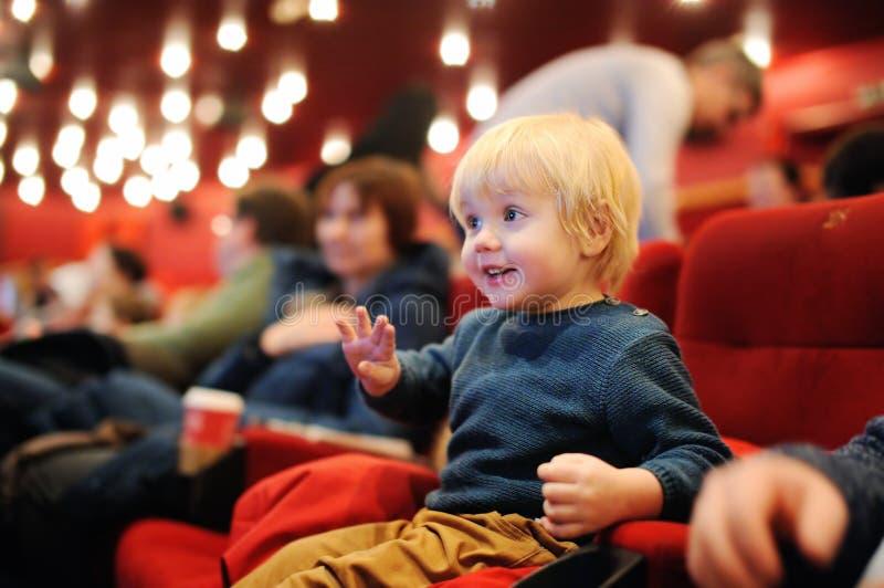 Filme de observação dos desenhos animados do menino bonito da criança no cinema foto de stock