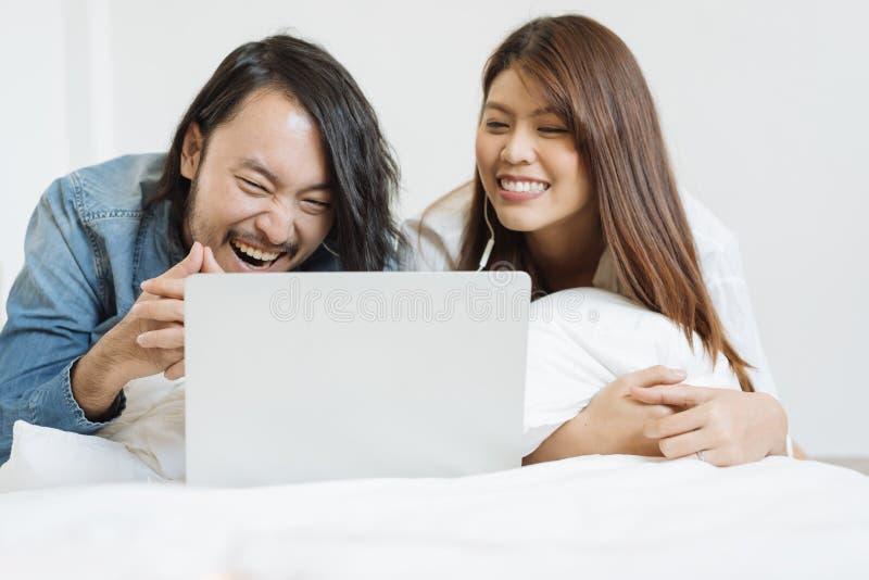 Filme de observação dos pares asiáticos novos com o portátil na cama imagens de stock royalty free