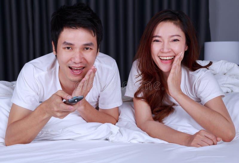 Filme de observação de riso dos pares na cama no quarto imagem de stock royalty free