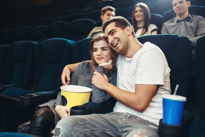Filme de observação de sorriso da comédia dos pares no cinema fotografia de stock