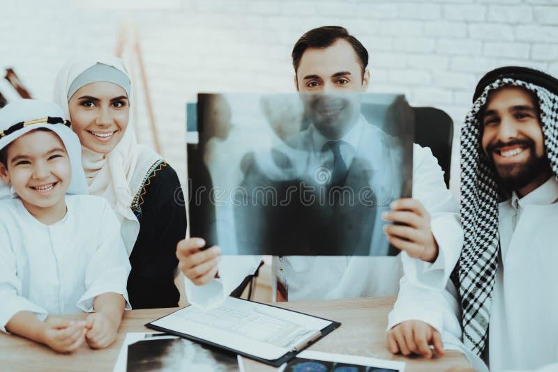 Filme de raio X árabe de sorriso da família e do doutor Holding fotos de stock royalty free