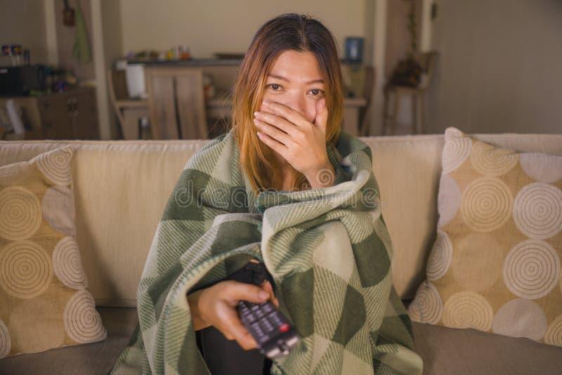 Filme de terror assustador de observação assustado ou surpreendido novo da televisão da mulher indonésia asiática coberto com a t imagem de stock royalty free