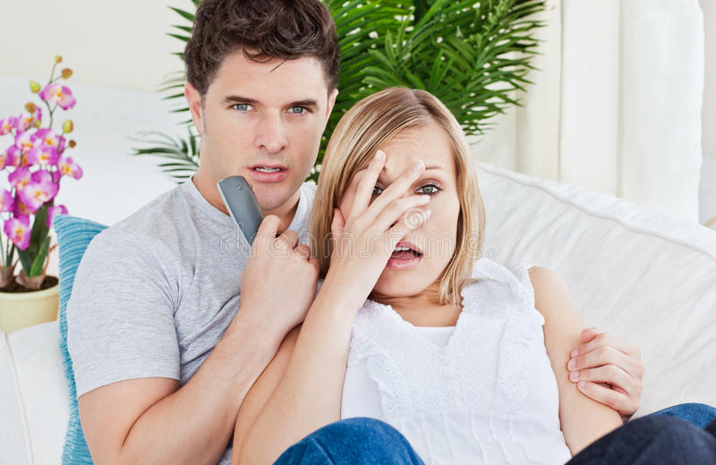 Filme de terror de observação Scared dos pares que encontra-se no sofá fotos de stock royalty free