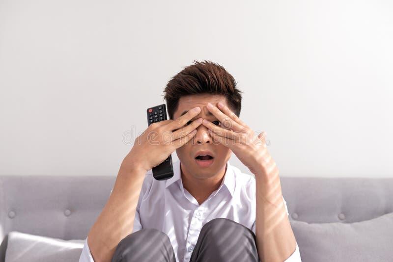 Filme de terror Homem novo consider?vel que guarda a tev? de controle remoto e olhando atrav?s de seus dedos ao sentar-se no sof? imagens de stock