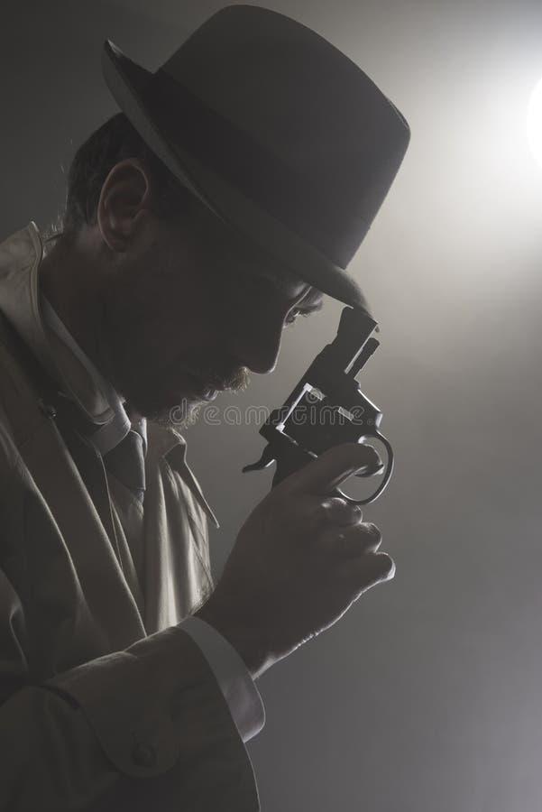 Filme noir: detetive na obscuridade com uma arma fotos de stock royalty free