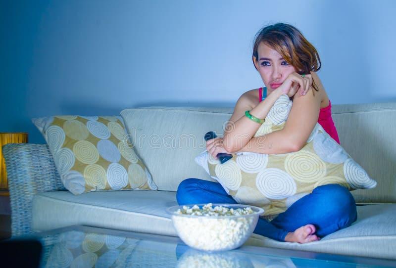 Filme romântico de observação do drama da mulher latin triste bonita nova que come a pipoca que senta em casa o sofá do sofá tard foto de stock