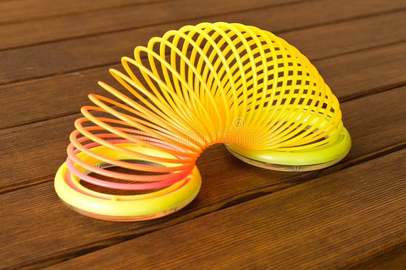 Filmed in September 1 , 2018 in Gomel. Toy plastic rainbow on a wooden table. Multi-colored spiral for the game royalty free stock photo