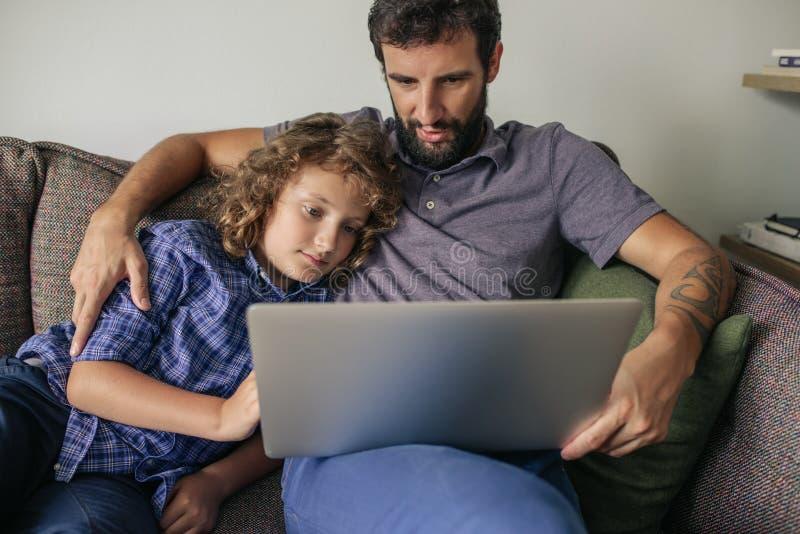 Filmes de observação do pai e do filho novo em um portátil imagens de stock