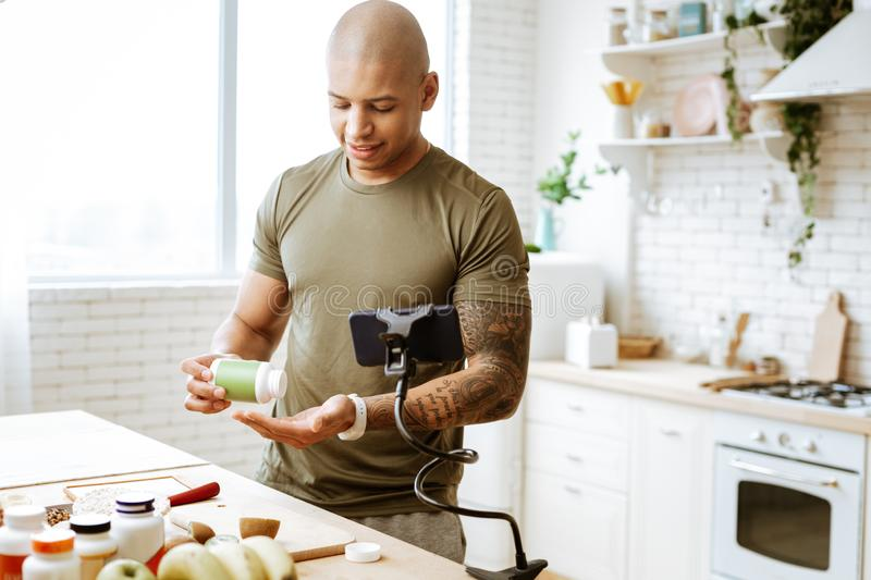 Bald bodybuilder taking vitamins while filming blog about diet. Filming blog. Bald bodybuilder wearing khaki t-shirt taking vitamins while filming blog about stock photos