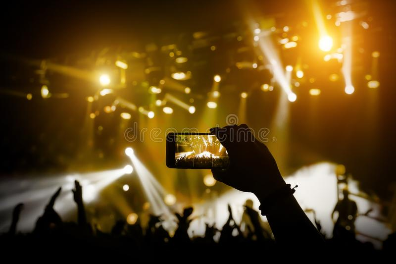 Filming a concert on mobile phone camera, yellow light. Of stage stock photos