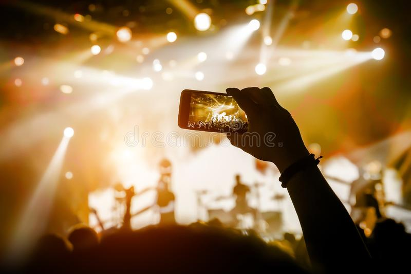 Filming a concert on mobile phone camera, yellow light. Of stage royalty free stock images