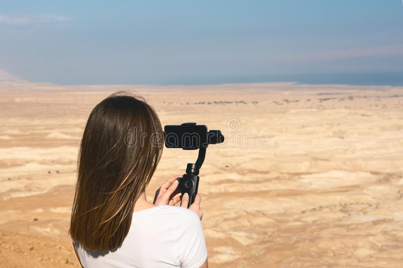 Young woman using gimbal in the desert of israel. Filming the desert lanscape with a phone and a gimbal. Dead sea in the background royalty free stock images