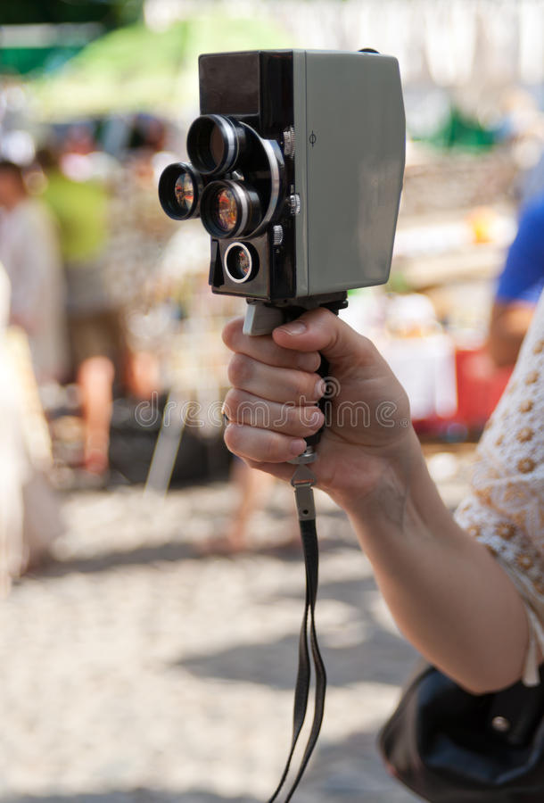 Filming with retro camera. Woman filming with retro camera outdoor royalty free stock photography