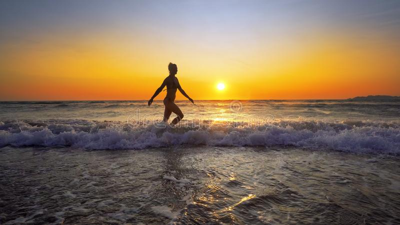 Filmiskt skott av den sexiga kvinnan som går i vatten på solnedgången royaltyfri foto