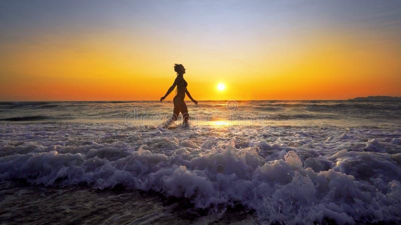 Filmiskt skott av kvinnan som går på vatten arkivbilder