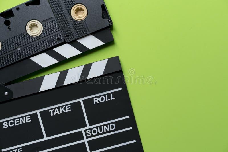 Filmklep en videocassettebanden op groene achtergrond royalty-vrije stock afbeeldingen