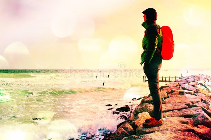 Filmkorn Högväxt fotvandrare i mörk sportswear med den sportiga ryggsäcken i regnrock på stranden, horisont med blå himmel med mo arkivfoto