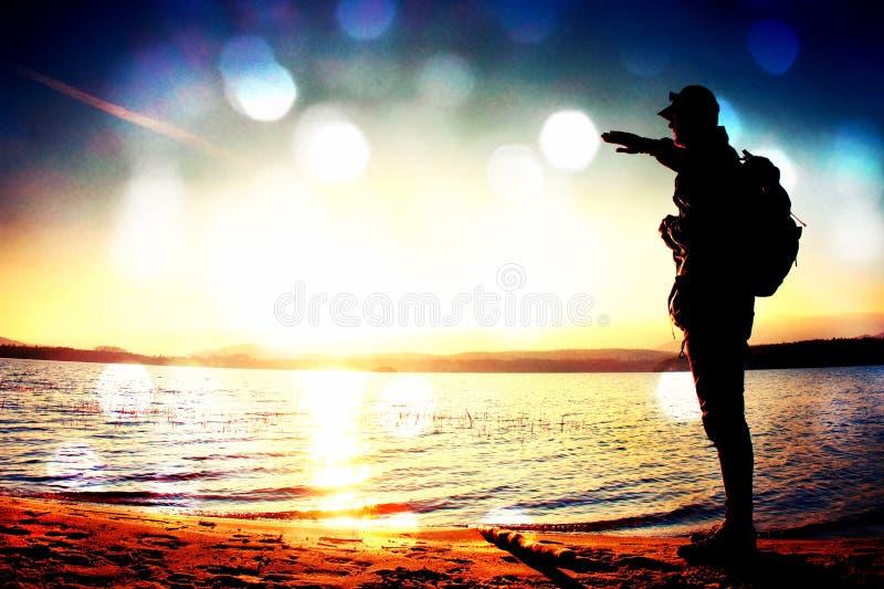 Filmkorn Lycklig man med handen i luften Den högväxta fotvandraren i mörk sportswear med sportiga ryggsäckställningar på stranden arkivbild
