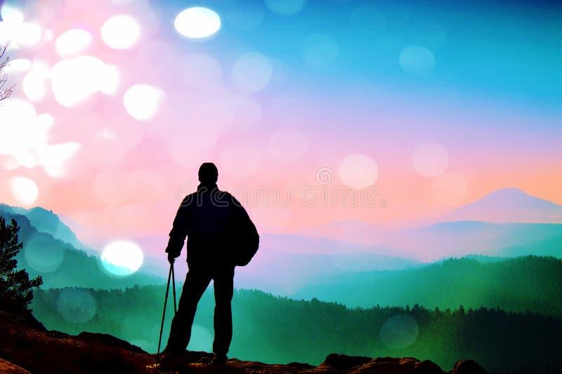 Filmkorn Schattenbild des Touristen mit Pfosten in der Hand Wanderer mit sportlichem Rucksackstand auf Felsen lizenzfreies stockfoto