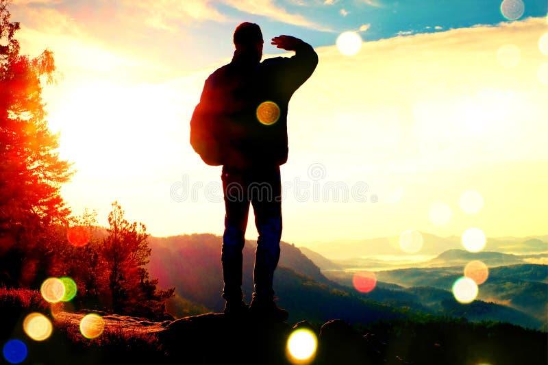 Filmkorn Schattenbild des touristischen sonnigen Frühlingstagesanbruchs in den felsigen Bergen Wanderer mit sportlichem Rucksacks lizenzfreie stockfotos