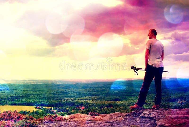 Filmkorrel Volwassen wandelaar met in hand polen De wandelaar neemt een rust op rotsachtig meningspunt boven vallei stock fotografie