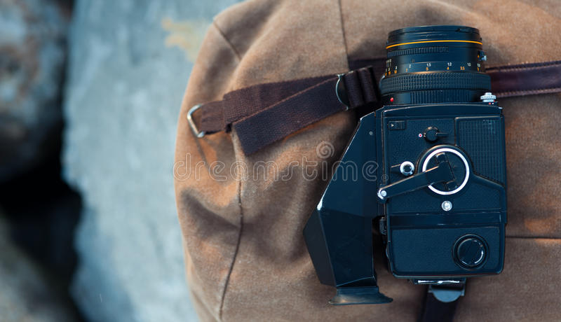 Filmmedelformatkameran ligger på stenarna mot bakgrunden av en kanfastappningryggsäck royaltyfri fotografi