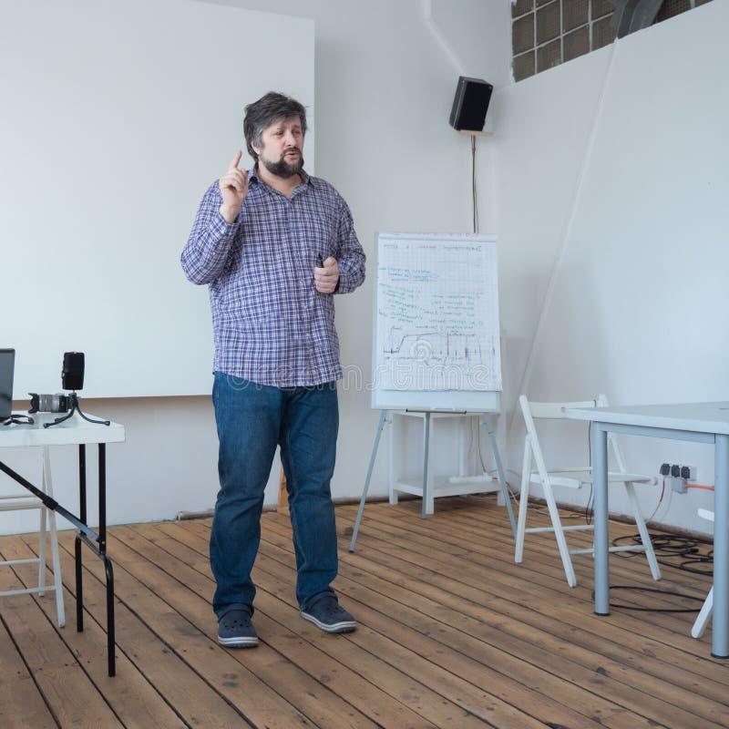 Filmowania szkolny pojęcie Profesor wykłada przy salą lekcyjną z drewnianą podłogą Kaukaska nauczyciel pozycja w wykładać zdjęcie royalty free