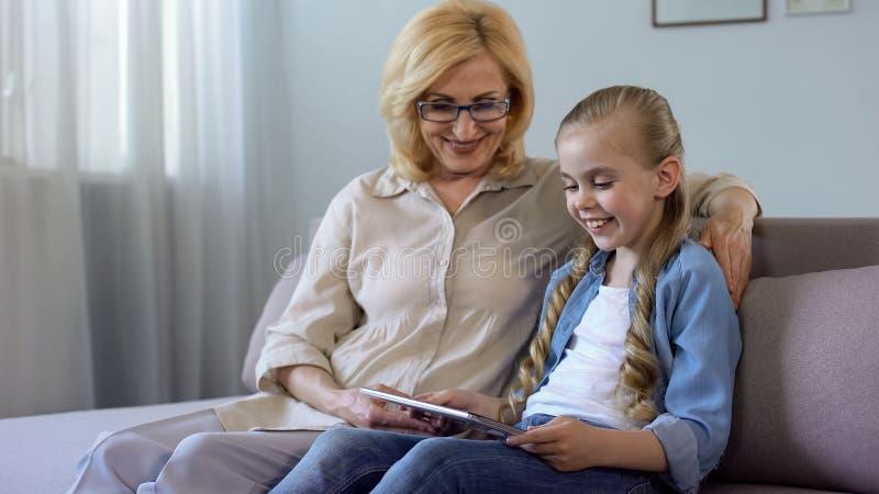 Films de observation de petite-fille aux cheveux longs sur le comprimé avec sa grand-mère sur le sofa photographie stock