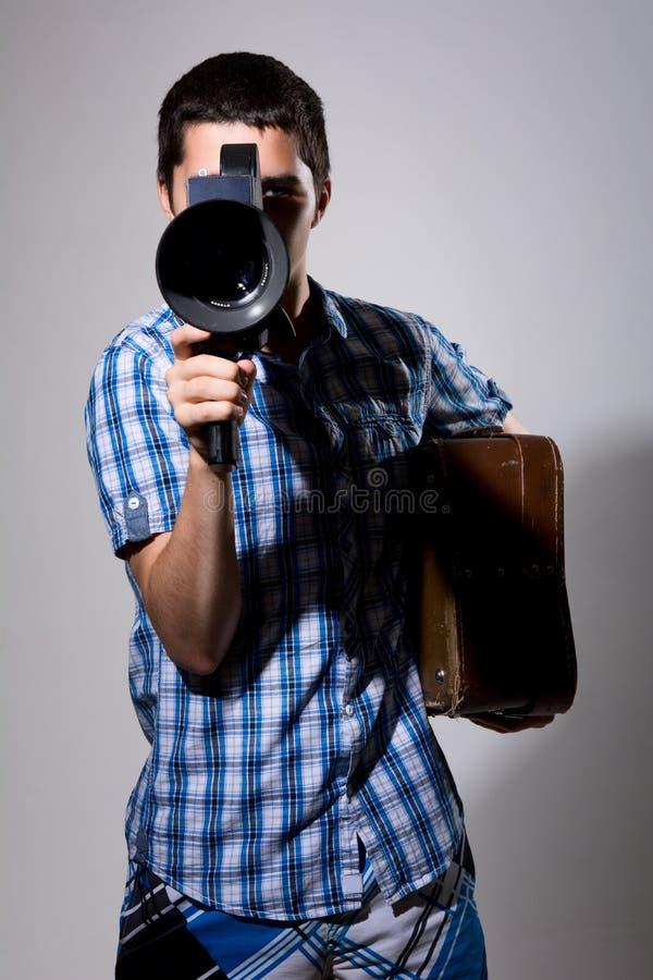 Filmskapare för ung man med den gamla filmkameran och en resväska i hans royaltyfri bild