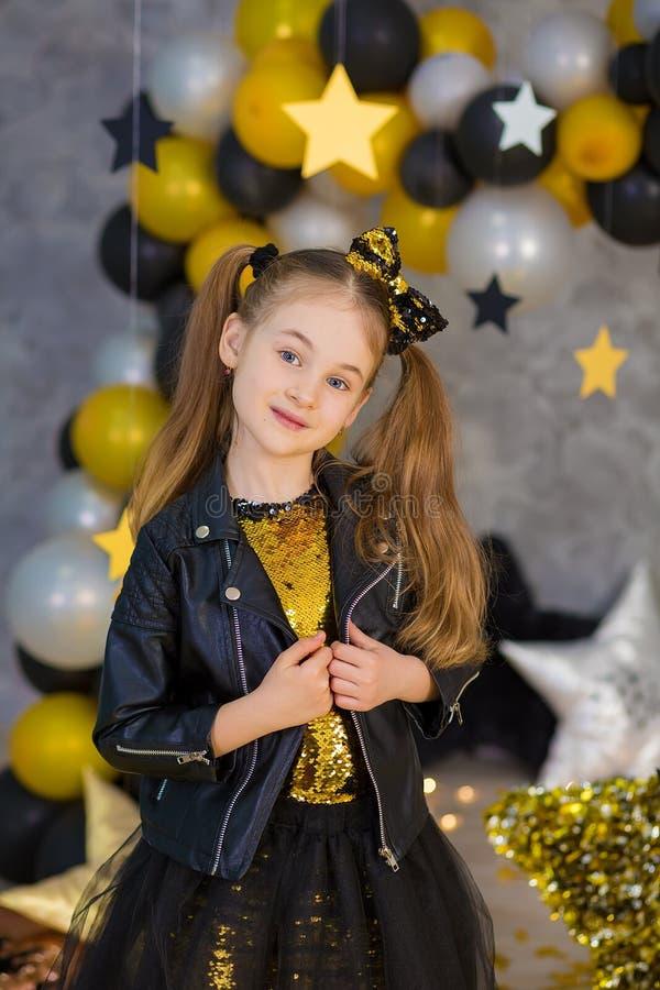 Filmsuperstern-Mädchenmodell, das im Studiotrieb mit goldenem Stern und bunten den baloons tragen stilvolles Goldluftiges Kleid m stockfotos