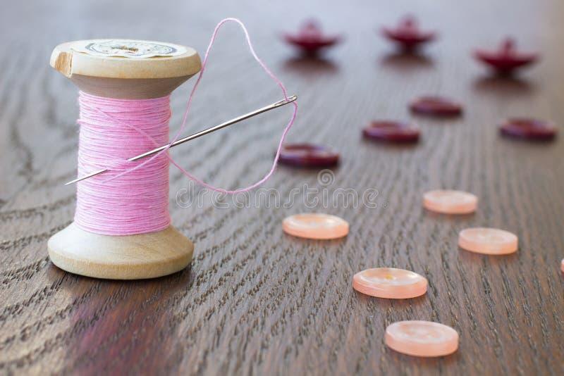 Filo di rosa della bobina con un ago Bottoni del chiaretto e di rosa fotografia stock libera da diritti