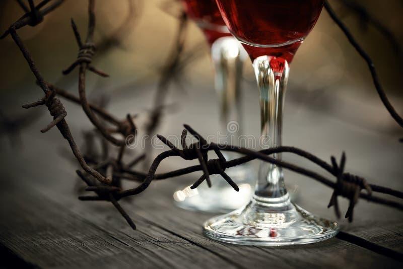 Filo spinato e vetri arrugginiti con vino rosso immagini stock libere da diritti