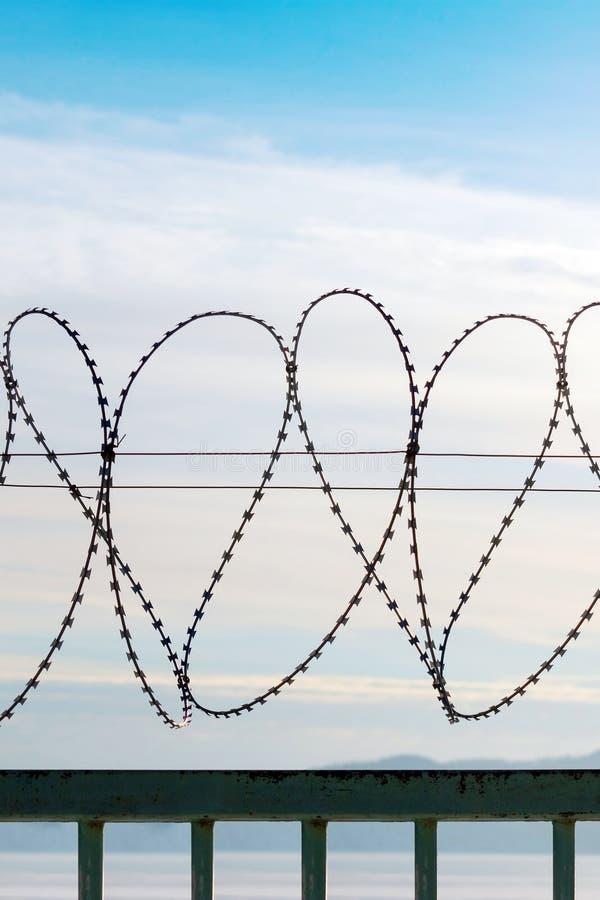 Filo spinato su un recinto del metallo Dietro il recinto è un cielo blu con le nuvole pennute fotografie stock