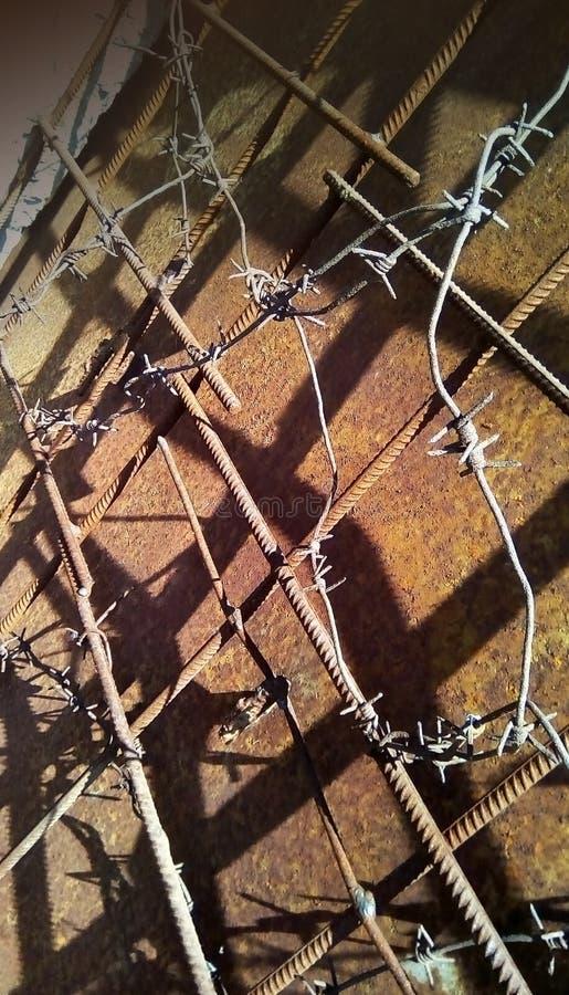 Filo spinato sul rinforzo del metallo su un fondo di ferro arrugginito fotografia stock libera da diritti