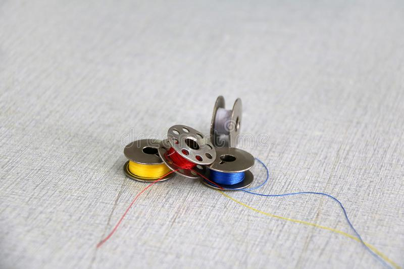 Filo variopinto nelle bobine, nel colore blu e bianco giallo rosso messi sulla macchina per cucire immagini stock