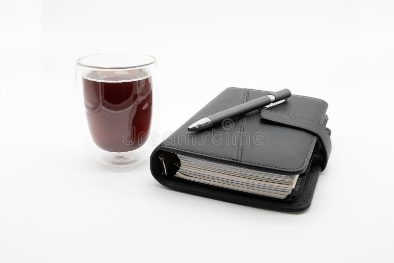 Filofax und Kaffee, lokalisiert auf wei?em Hintergrund lizenzfreie stockfotografie