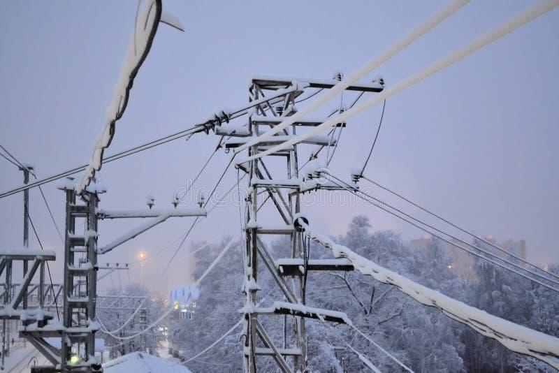 Fils électriques de entrelacement dans la neige Début de la matinée Russie photographie stock libre de droits
