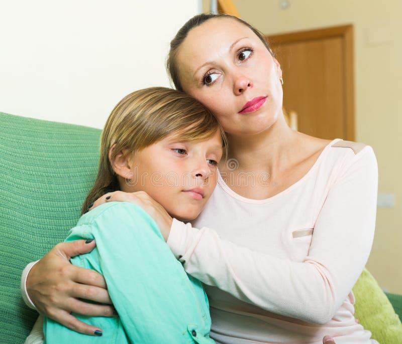 Fils adolescent pleurant de consolation de mère à la maison photos libres de droits