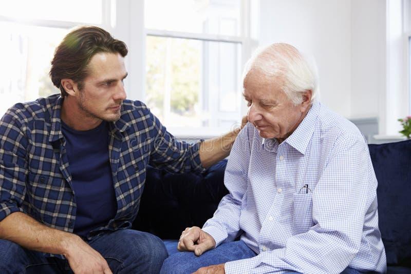 Fils adulte parlant au père déprimé At Home image stock