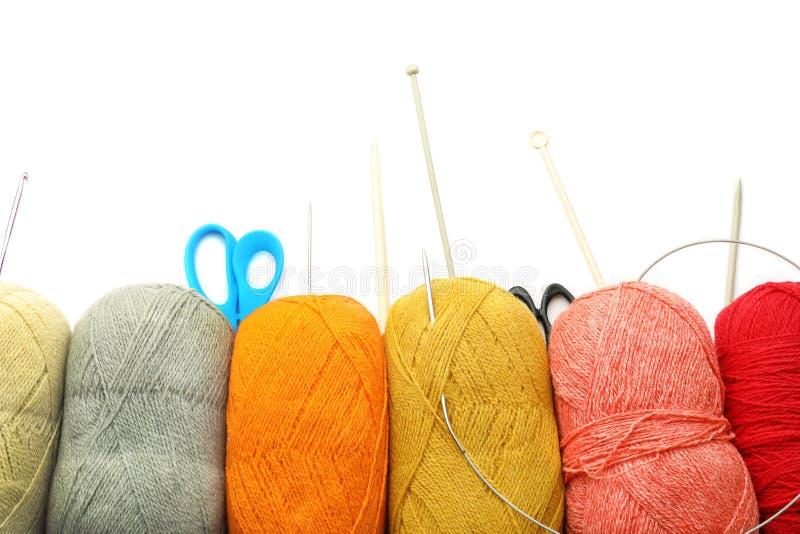 Fils, ciseaux et aiguilles de tricotage sur le fond blanc image libre de droits