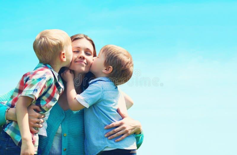 Fils d'enfants de la famille deux de portrait embrassant la maman, jour du ` s de mère, bleu photographie stock