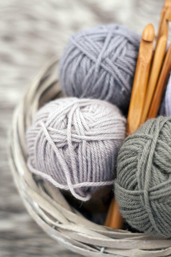 Fils dans le panier avec des crochets de crochet dans des couleurs harmonieuses tricotant, approvisionnements faisants du crochet photos stock